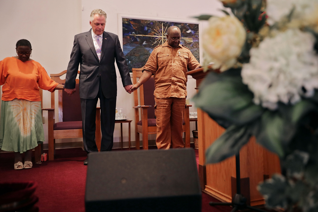 Virginia Gov. Terry McAuliffe holds hands and prays with Dr. Alvin Edwards, pastor of Mt. Zion First African Baptist Church on August 13, 2017 in Charlottesville, Virginia.
