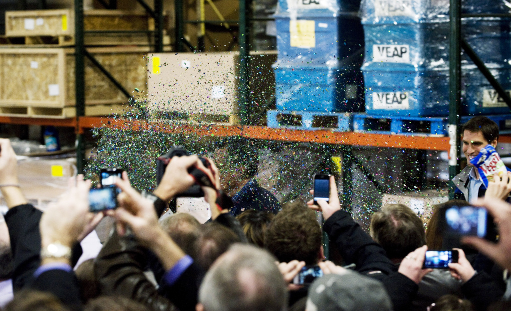 Glitter is tossed into the air as Republican presidential candidate and former Massachusets Gov. Mitt Romney makes his way toward the stage during a rally at Freightmasters February 1, 2012 in Eagan, Minnesota.