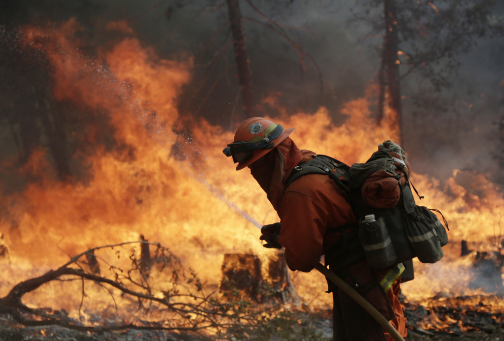 A firefighter with the Gabilan Camp crew hoses down hot spots during a controlled burn to fight the King Fire on Monday, Sept. 22, 2014, near Placerville, Calif. Crews scrambled Monday to extend control lines around a massive Northern California wildfire threatening thousands of homes as they braced for strong, erratic winds similar to when the blaze doubled in size a week before. (AP Photo/Marcio Jose Sanchez)