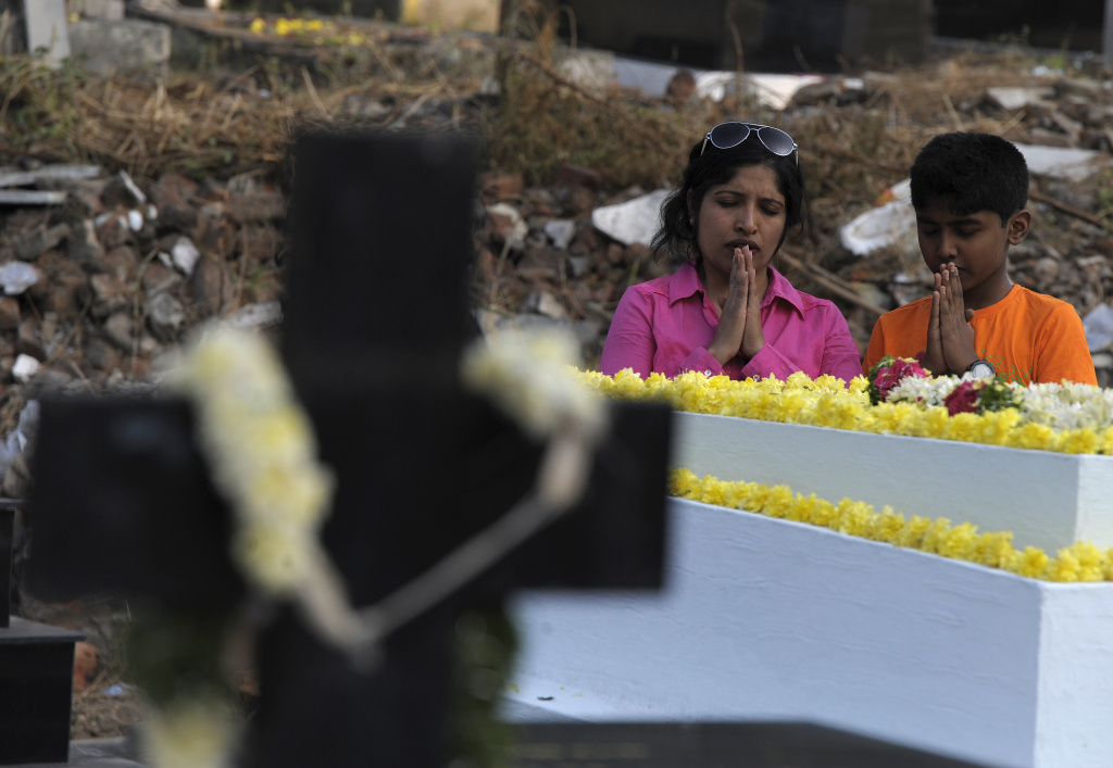Indian Catholics offer prayers at the graves of their family members at a cemetery during All Souls Day in Hyderabad on November 2, 2016.