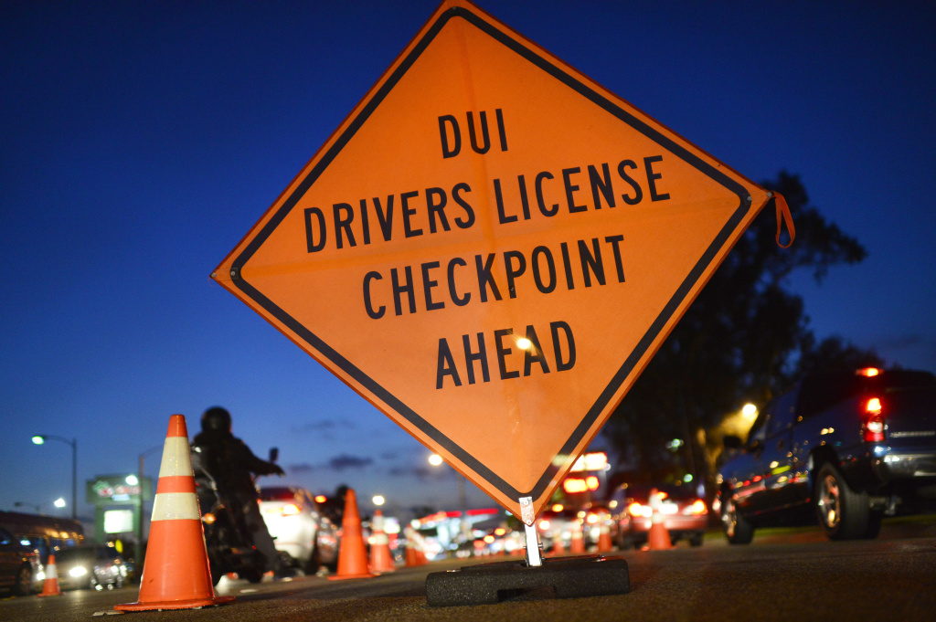 A road sign and cones lead westbound drivers on Alondra Boulevard through a DUI checkpoint manned by Los Angeles County Sheriff's Department deputies March 6, 2014 in Bellflower.