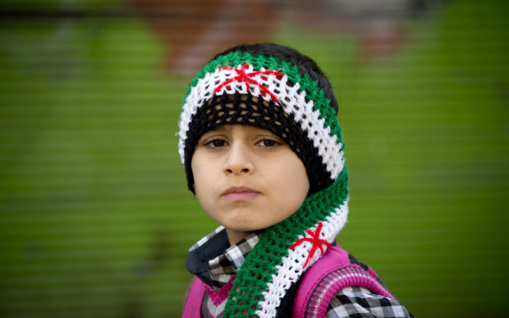 A Syrian boy looks over at a rebel fighter in the northern town of Darkush on December 14, 2012.