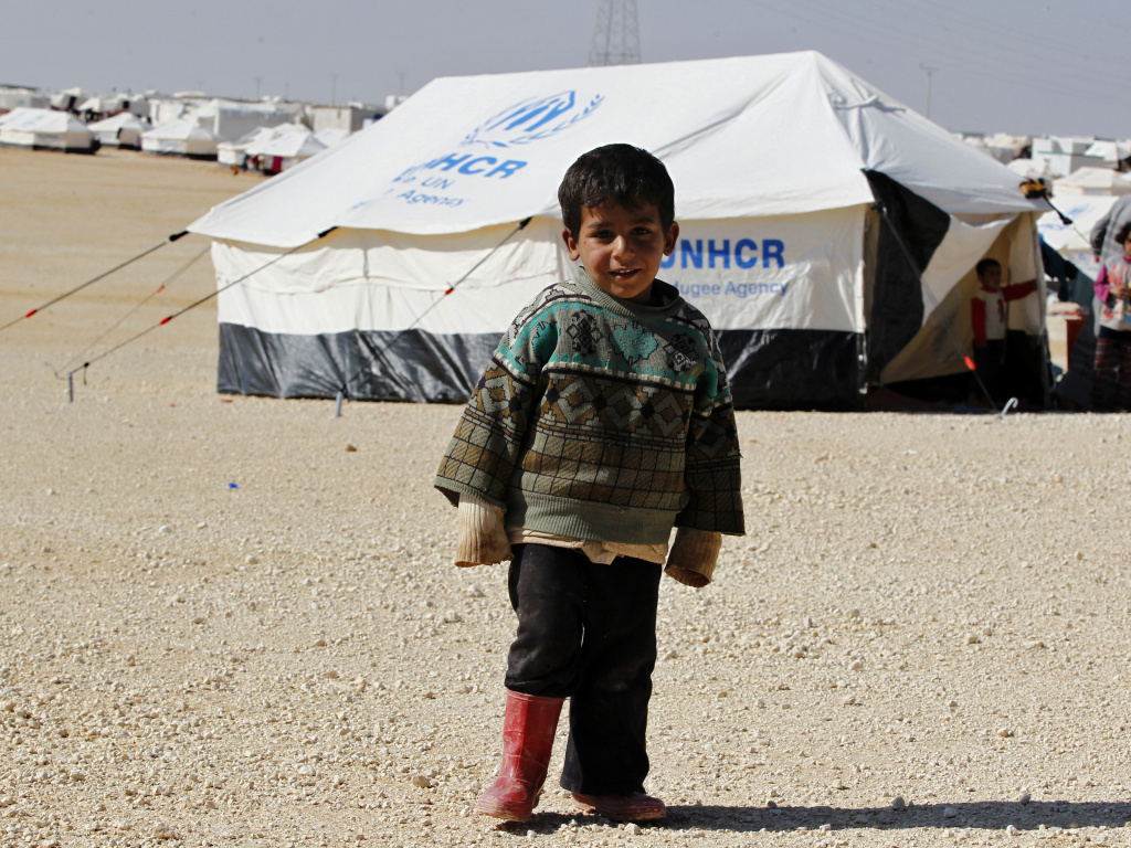 FILE: A Syrian refugee boy stands outside his tent in a refugee camp in the Jordanian city of Mafraq, near the border with Syria. A recent U.S. District Court order has opened the door for more refugees to arrive in the United States who would otherwise be barred by President Trump's temporary travel ban.