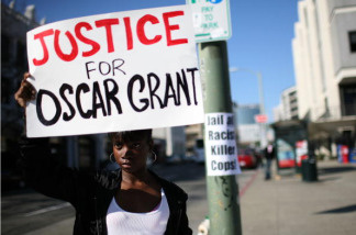 Javone Sloan holds a sign saying 'Justice For Oscar Grant' during a protest of court case involving a Bay Area transit officer