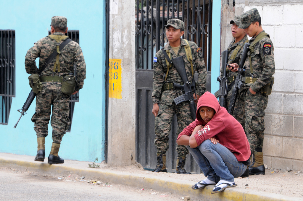 Armed army soldiers await to embark on city buses in Tegucigalpa, on March 11, 2014, during a deployment of troops in the urban transport in an attempt to stop violence against commuters and drivers from criminal gangs.