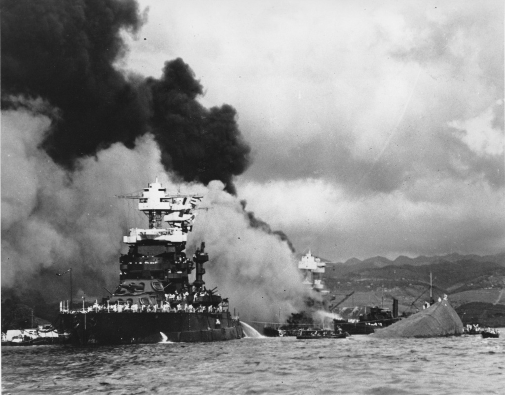 File: in this Dec. 7, 1941 file photo, the battleship USS West Virginia, center, begins to sink after suffering heavy damage, while the USS Maryland, left, is still afloat in Pearl Harbor, Oahu, Hawaii. The capsized USS Oklahoma is at right.