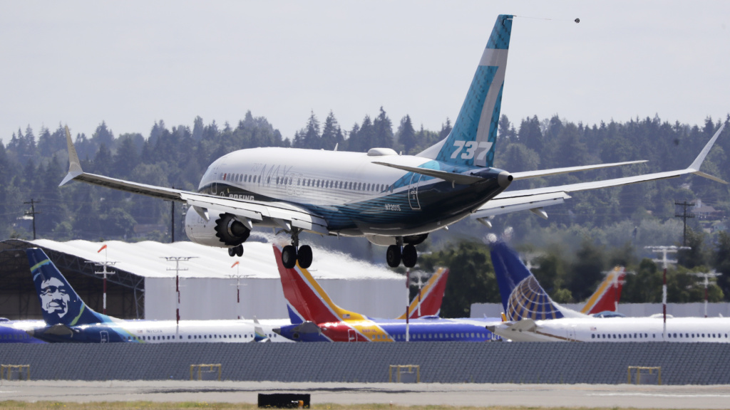 A Boeing 737 Max heads to a landing past grounded 737 Max aircraft at Boeing Field following a test flight Monday in Seattle. The jet took off from Boeing Field earlier in the day, the start of three days of re-certification test flights that mark a step toward returning the aircraft to passenger service.