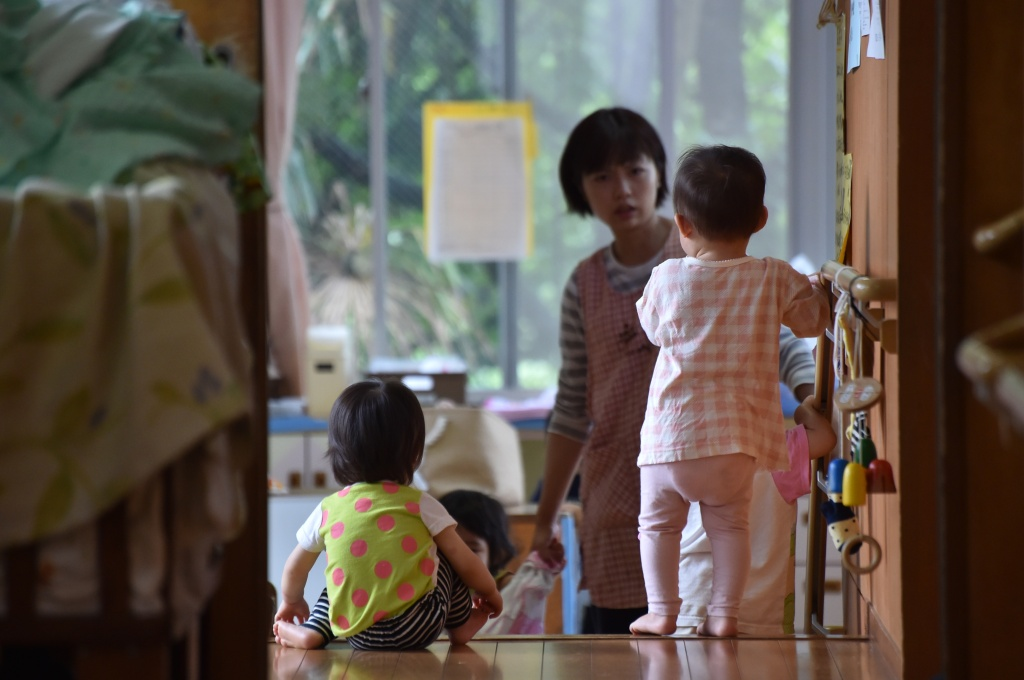 This picture taken on June 29, 2016 shows an employee of an official nursery school taking care of young children in Yokohama, Japan.