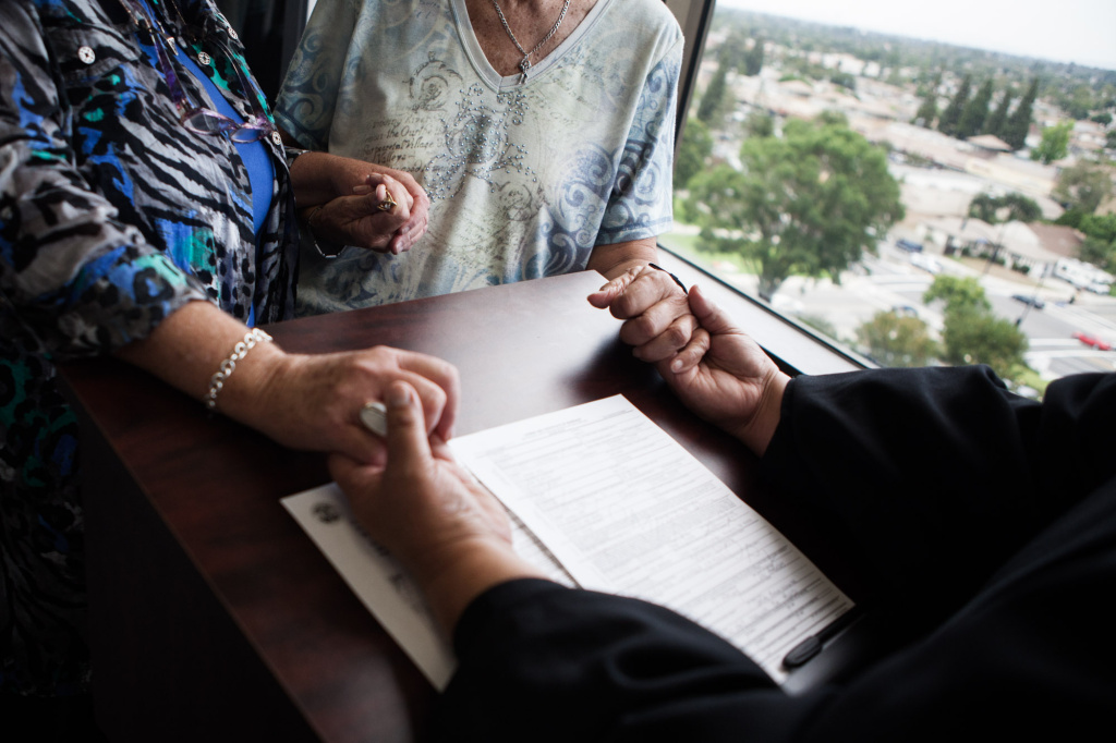 Mari Lopez, a Los Angeles deputy commissioner, holds the hands of Lilyanne McCoy and Sandra Schicora of Lakewood during the marriage ceremony at the LA County Clerk's office in Norwalk. San Diego's county clerk has said the California attorney general doesn't have the authority to direct him to issue marriage licenses to same-sex couples and is seeking clarification from the state Supreme Court.