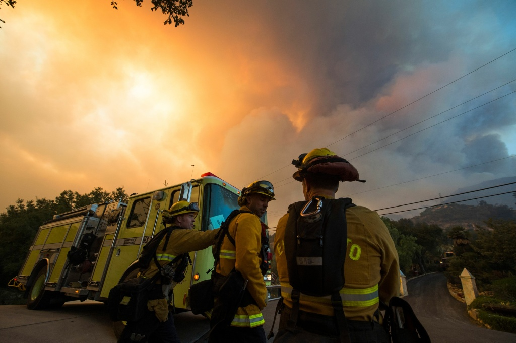 Firefighters from the Governors Office of Emergency Services monitor the advance of smoke and flames from the Thomas Fire on December 16, 2017 in Montecito, California.
