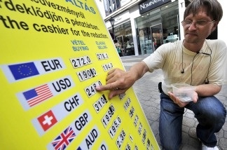 An employee changes the numbers of the currency information board in front of an exchange office on Aug. 8th in Budapest. The Swiss franc remained at its highs against the dollar, changing hands at 0.7594 to the dollar.