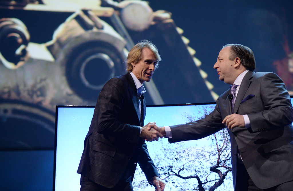Director Michael Bay is greeted by Samsung Electronics America Executive VP Joe Stinziano on stage at the Samsung press event at the Mandalay Bay Convention Center for the 2014 International CES on January 6, 2014 in Las Vegas, Nevada. Bay abruptly walked off the stage after a teleprompter malfunctioned and Bay was unable to ad-lib to continue the presentation.