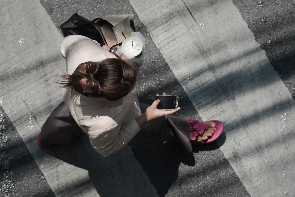 This picture taken on March 20, 2013 shows a woman looking at her smartphone while walking in a street in Bangkok.