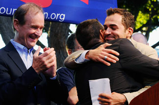 Plaintiffs Paul Katami (L) hugs his partner Jeff Zarrillo as their lawyer David Boies (R) looks on during a rally to celebrate the ruling to overturn Proposition 8 on August 4, 2010 in West Hollywood, California.