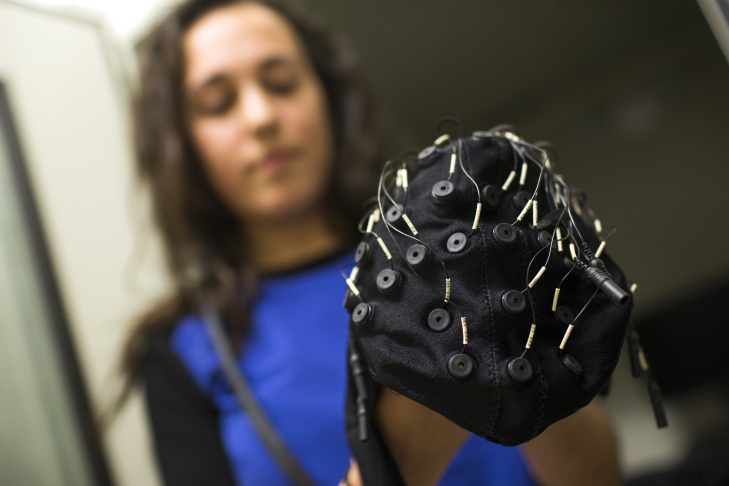 Cara Fesjian, a student researcher at USC, holds an electroencephalography cap used to map children's brain activity at the Brain and Creativity Institute on Wednesday, March 11, 2015. The institute has released a report of interim research findings from a five-year study looking at the emotional, social and cognitive effects of musical training on childhood brain development.