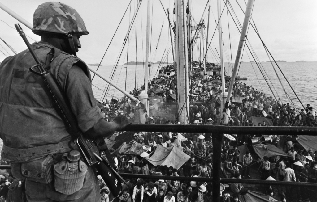 A picture released on May 05, 1975 shows an GI watching South Vietnamese refugees crowding a US Navy boat off the coasts of Vietnam at the end of Vietnamese war. AFP PHOTO        (Photo credit should read -/AFP/Getty Images)