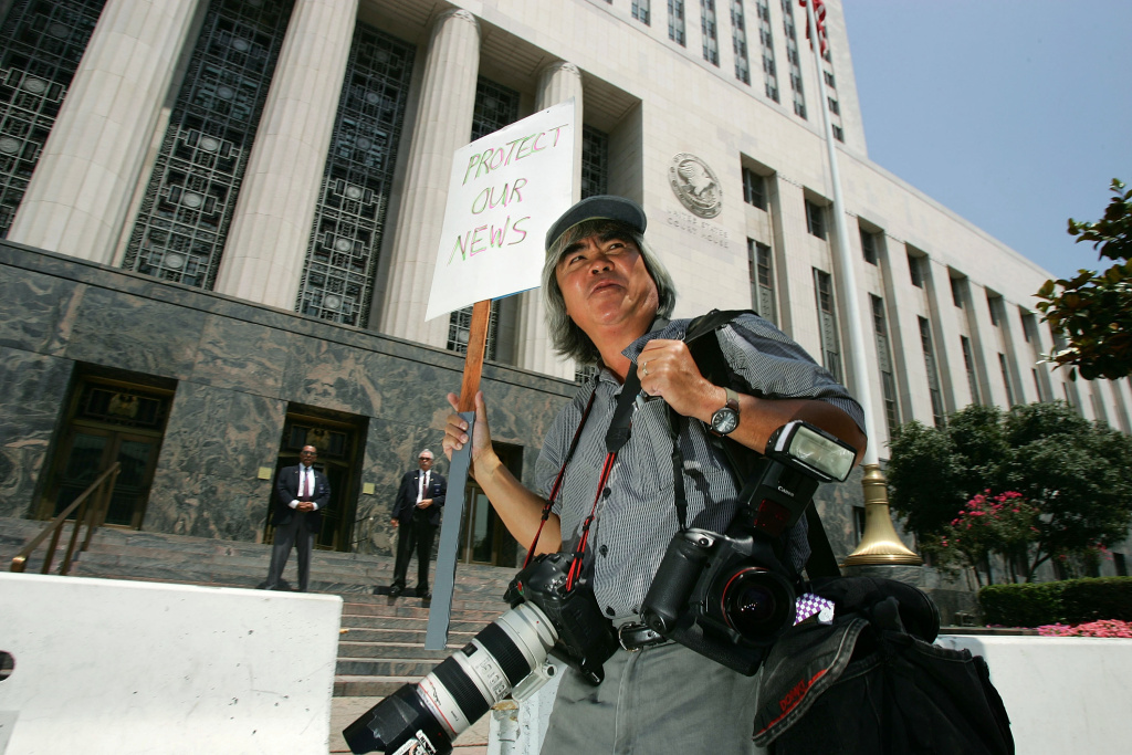 Pulitzer prize-winning photojournalist Nick Ut carries a sign as journalists demonstrate in front of the federal courthouse July 6, 2005 in Los Angeles, California.