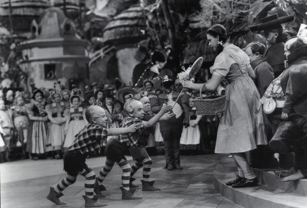 Jerry Maren as a Lollipop Guild Member presents Judy Garland with a gift in the 1939 film, 'The Wizard of Oz.'