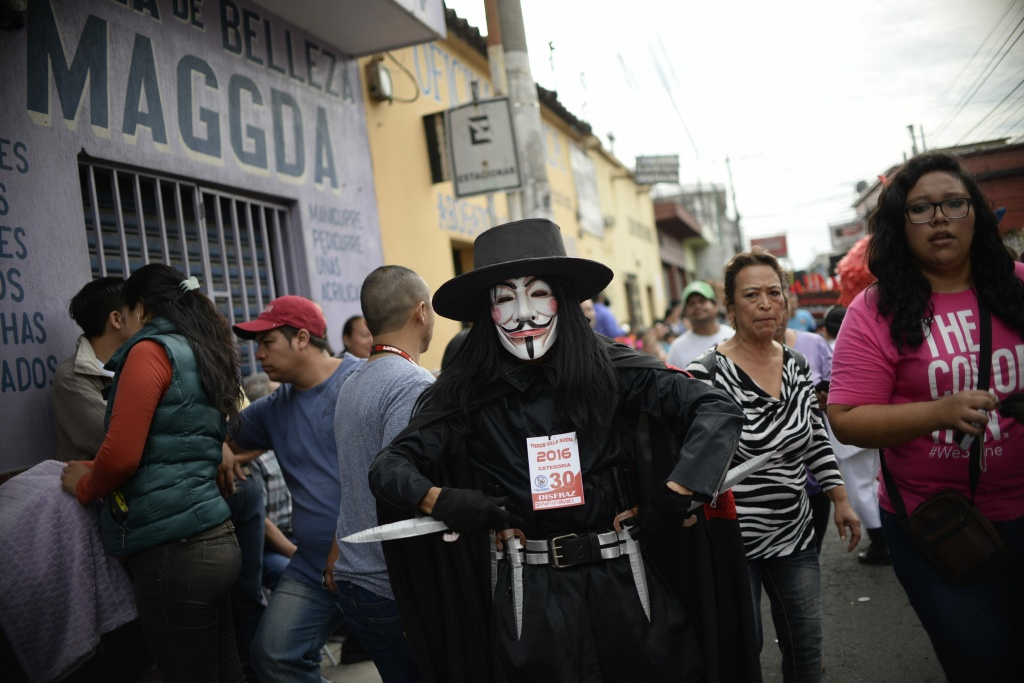 A reveler with a Guy Fawkes mask takes part in the traditional