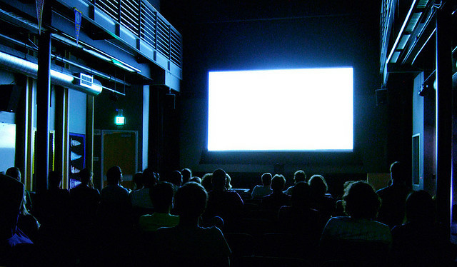 File: A crowd watching a movie on a big projector screen.