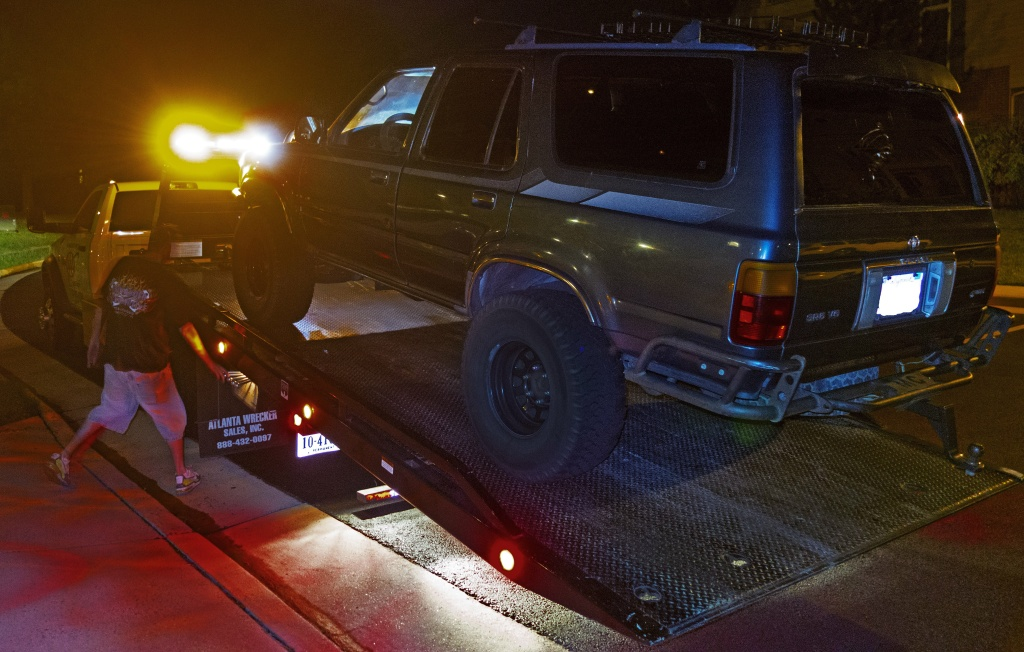 A tow truck driver prepares to tow an SUV.