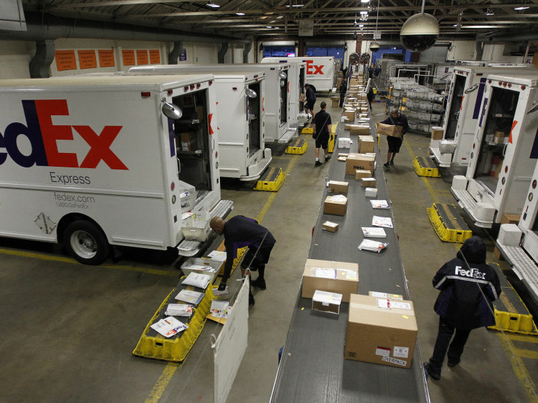 Couriers load packages onto vehicles as other packages move down the belt at the FedEx station in Marina del Rey, Calif. Cyber Monday sales are expected to total $1.5 billion or more, according to research firm comScore.