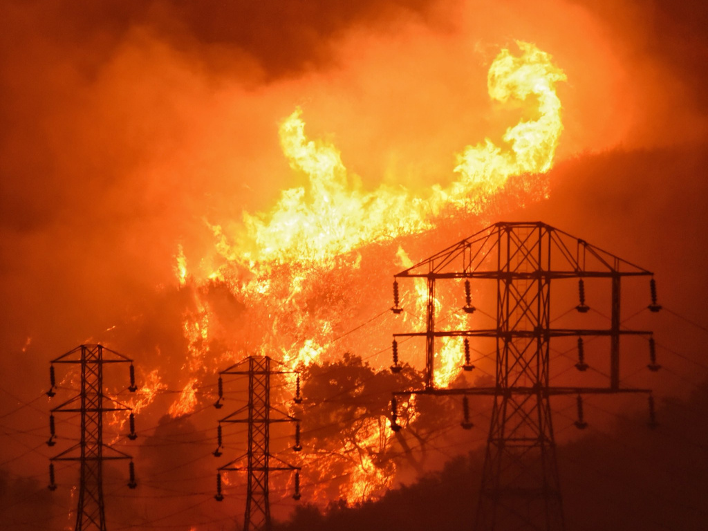 Flames burn near power lines in Montecito, Calif. State fire officials say power lines coming into contact with trees have sparked multiple Northern California wildfires in recent years. PG&E filed for bankruptcy today.