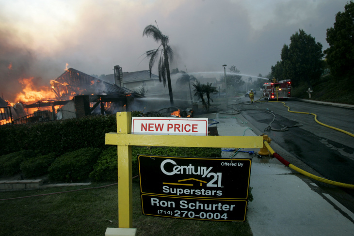 Firefighters spray water on a burning home November 15, 2008 in Yorba Linda, California.  (Photo by Sandy Huffaker/Getty Images)