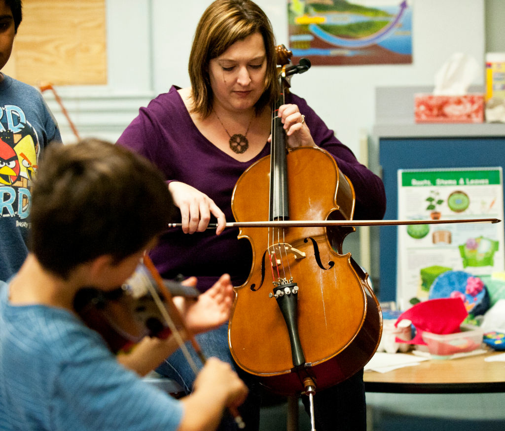 Lydia Tseng, music director of the Prelude Program, tunes instruments for students before an Elemental Strings class at McKinley Elementary School in Santa Monica.