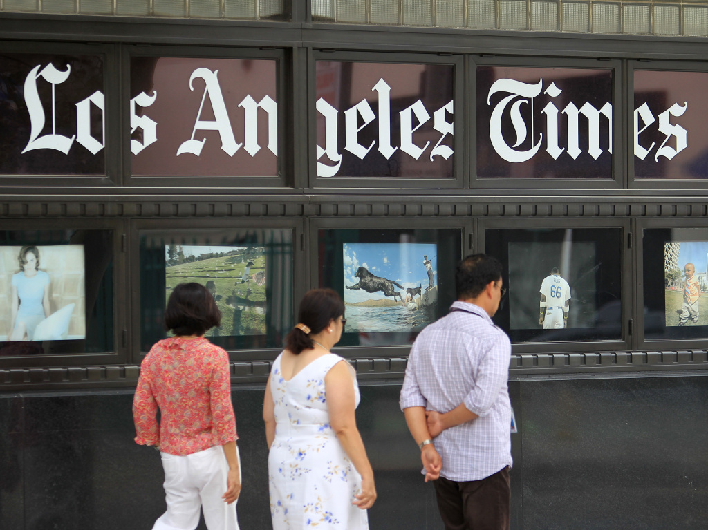 Pedestrians pass photos displayed on the <em>Los Angeles Times</em> building in 2013. Business Editor Kimi Yoshino returned to the newsroom Thursday.