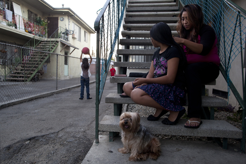 Claudia Chi Ku braids the hair of her daughter, Leslie Soriano, 11, as her other children play outside of their apartment in Pico Union.