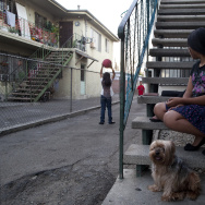Claudia Chi Ku braids the hair of her daughter, Leslie Soriano, 11, as her other children play outside of their apartment in Pico Union. Chi Ku supports her family while working as a cashier at a restaurant in the neighborhood.