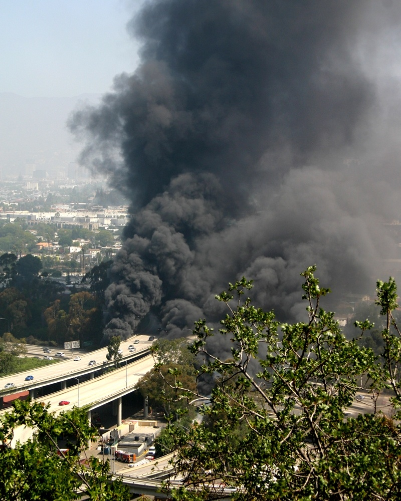 Smoke billows from a fire Saturday July 13, 2013 in Los Angeles, after a tanker truck flipped, spilled its load of gasoline and caught fire, snarling traffic for miles.