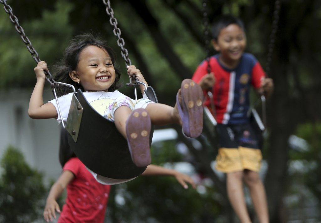 Indonesian children play on swings at a park in Jakarta, Indonesia, Friday. April. 4. 2014.