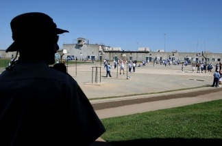 A California Department of Corrections officer looks on as inmates at the Mule Creek State Prison exercise in the yard in Ione, California.