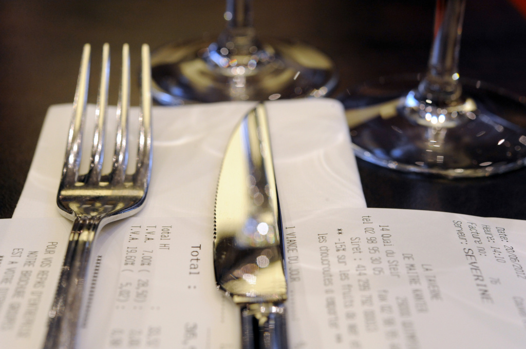 A picture taken on June 20, 2012 at a restaurant in Quimper, western France, shows fork and knife on an invoice indicating the two Value-added tax (VAT) 7.0 and 19.6 percent rate.