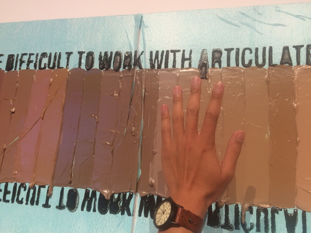 A piece by artist April Bey. KPCC's Leo Duran holds up his own hand to see what adjectives are associated with his skin tone.