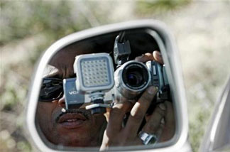In this March 16, 2008, file photo, paparazzi Craig Williams, of Hollywood.TV, is seen through the side mirror during a stake out near Britney Spears' house in Los Angeles. Newly signed legislation would increase penalties for actions that include taking photos and video of a child without consent and in a harassing manner.