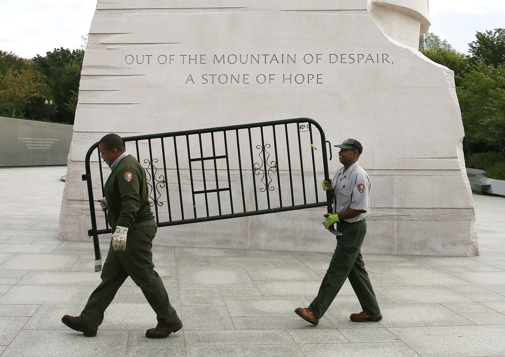 U.S. Park Service workers carry a barricade that was used to close the Martin Luther King Memorial on the morning after a bipartisan bill was passed by the House and the Senate to reopen the government and raise the debt limit.