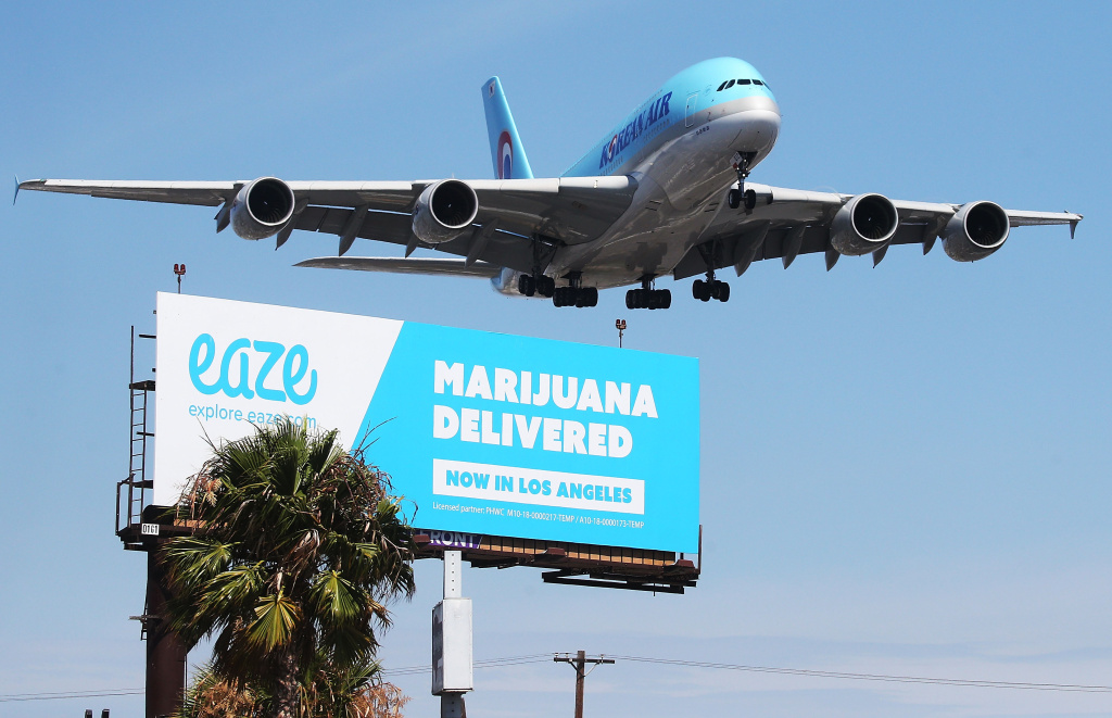 An airplane descends to land at Los Angeles International Airport above a billboard advertising the marijuana delivery service Eaze on July 12, 2018 in Los Angeles, California.