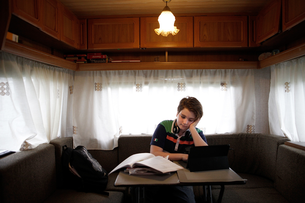 Angel Nicols, 12, does his school work in the tiny caravan he shares with his mother as they travel around England with Mr. Fips' Wonder Circus on April 7, 2014.
