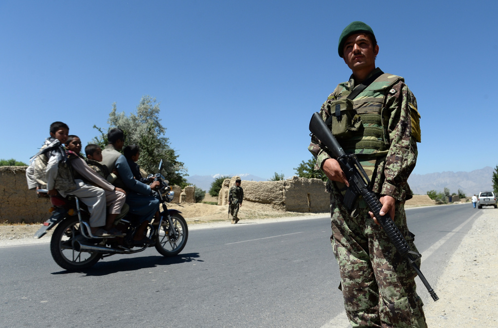 Afghan men on a motorcycle drive past Afghan National Army (ANA) soldiers on guard outside Bagram military base, 50 kms north of Kabul on June 19, 2013. The Taliban killed four US troops in an attack on June 19.