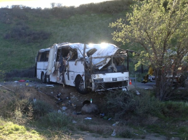 The sun rises over the remains of a tour bus that crashed in Yucaipa on Feb. 3. Seven people were killed and 20 injured.