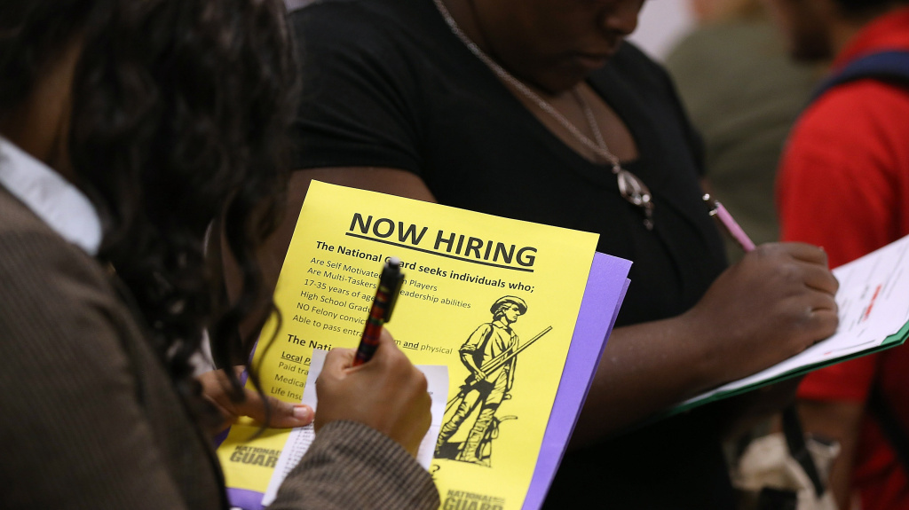 File photo: Attendees of a job fair in California in October fill out paperwork.
