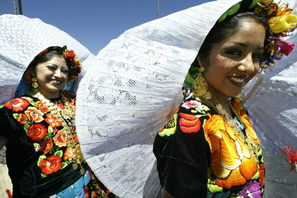 Two girls wearing Oaxacan traditional costumes prepare to enter the stage during the celebrations of the Guelaguetza in Los Angeles, 03 August 2003.