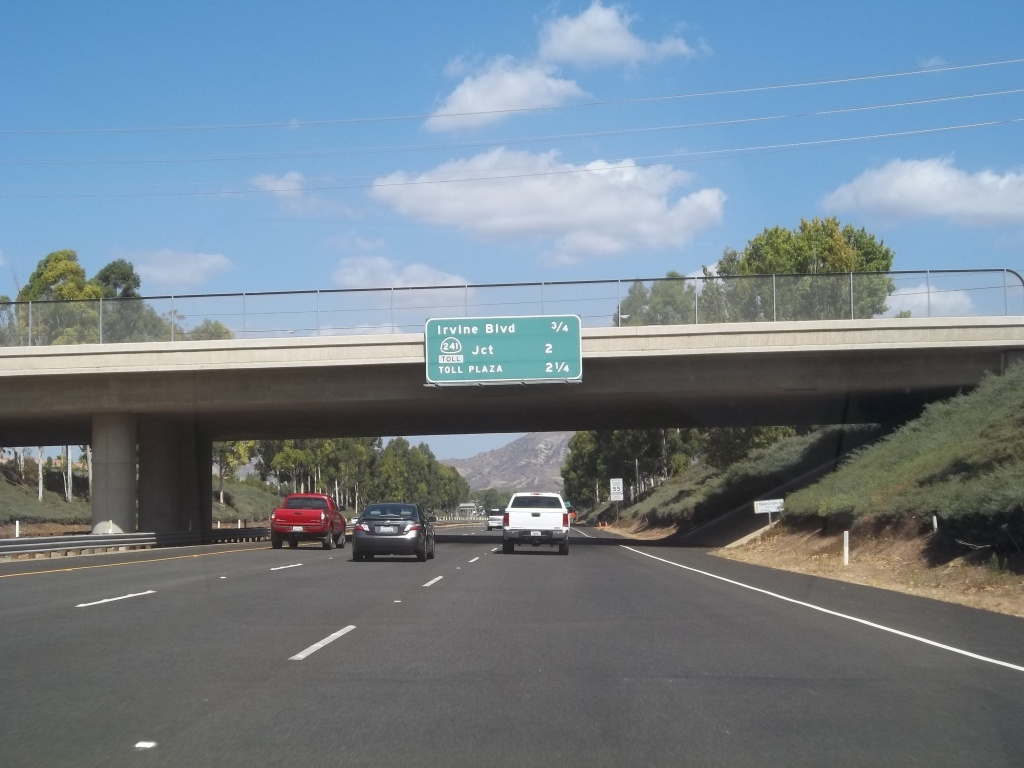 Photo shows northbound California State Route 133 and sign stating distances to Irvine Boulevard, Route 241 Toll and Toll Plaza.