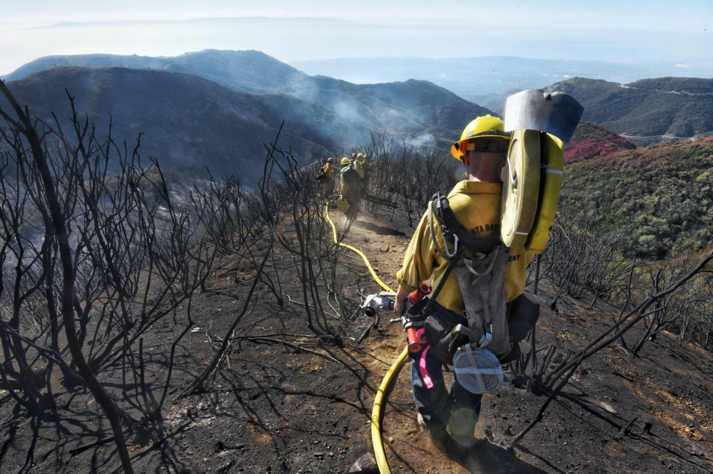 In this photo provided by the Santa Barbara County Fire Department, Santa Barbara County Firefighters haul dozens of pounds of hose and equipment down steep terrain below E. Camino Cielo to root out and extinguish smoldering hot spots in Santa Barbara, Calif., Tuesday, Dec. 19, 2017. Officials estimate that the Thomas Fire will grow to become the biggest in California history before full containment.