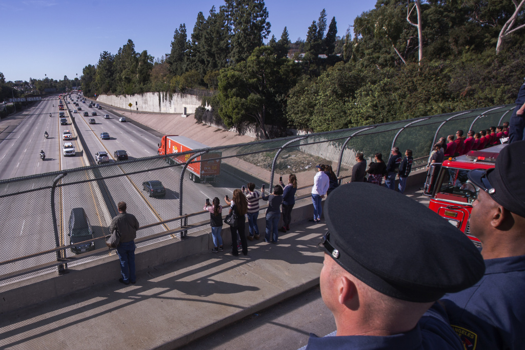 Firefighters and bystanders watch as a procession carries the body of Cory Iverson, 32, a fire engineer for Cal Fire San Diego who died fighting the Thomas Fire, on December 17, 2017.