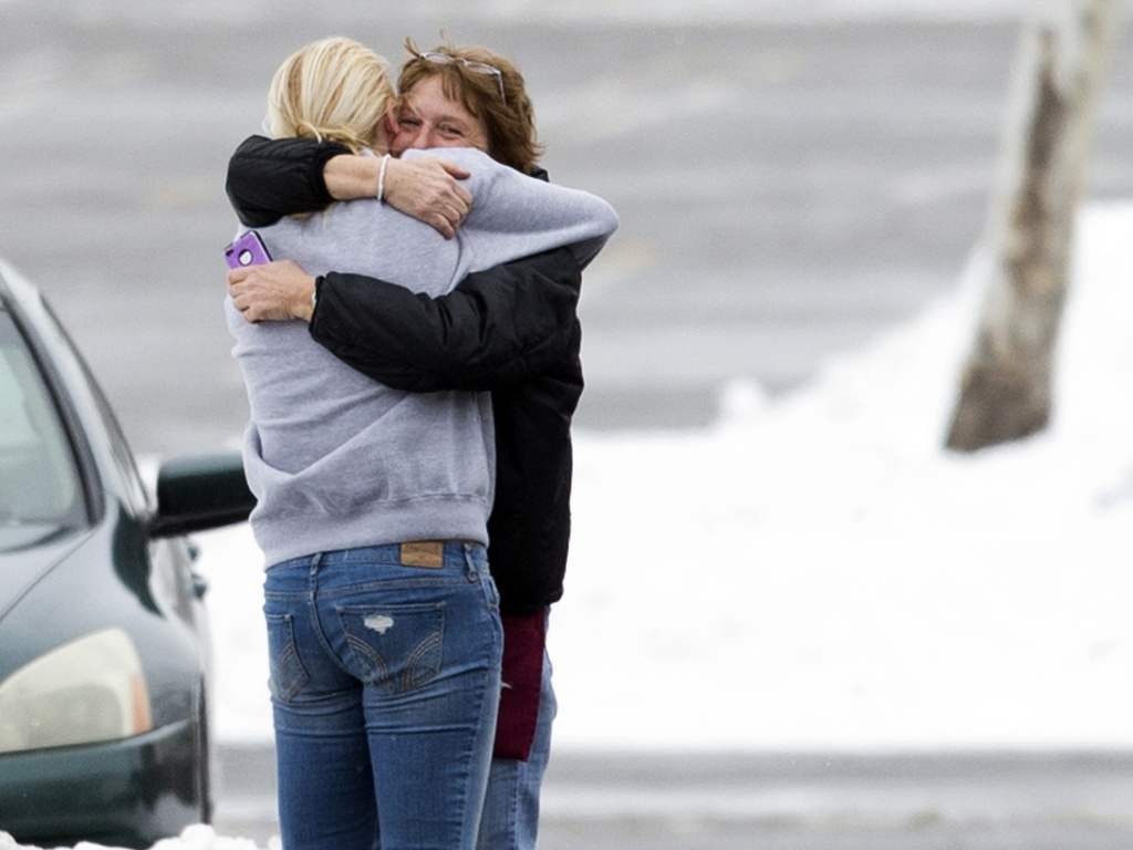 Two people embrace in the parking lot at the scene of a shooting at The Mall in Columbia on Saturday, in Columbia, Md.