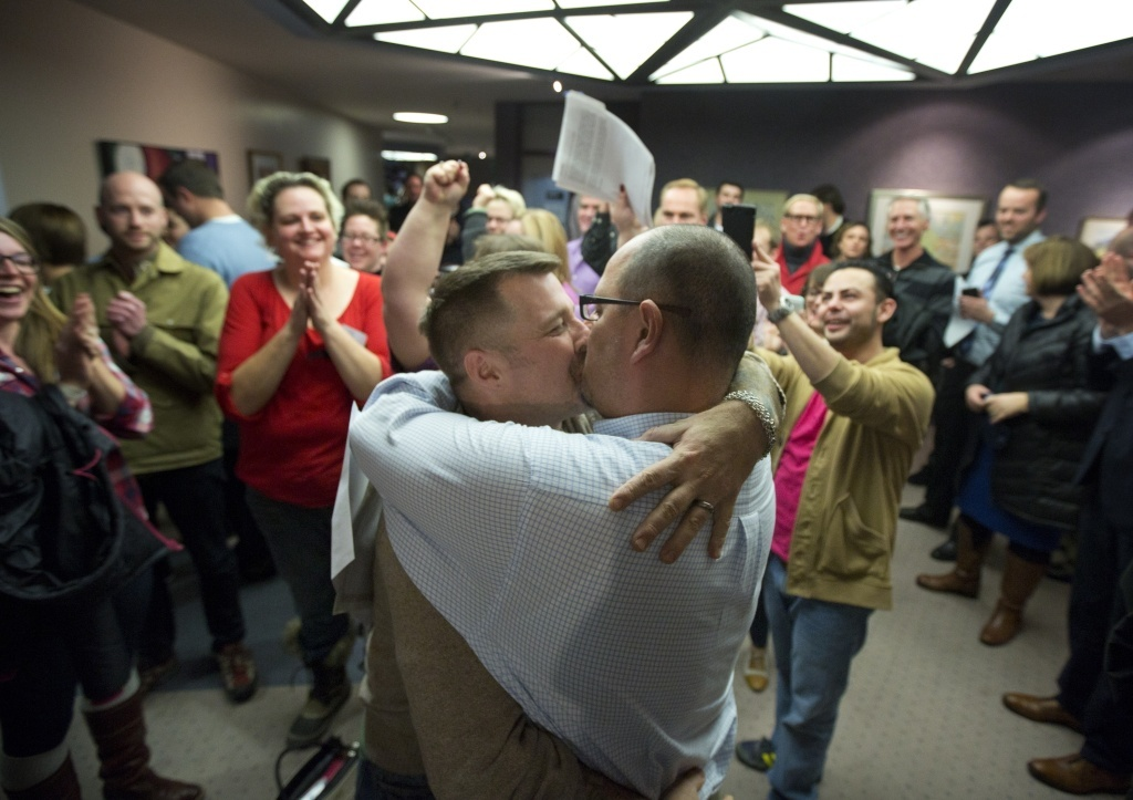 Chris Serrano, left, and Clifton Webb kiss after being married, as people wait in line to get licenses outside of the marriage division of the Salt Lake County Clerk's Office in Salt Lake City, on Friday.